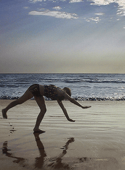 Picture of Jennifer Ann Crecente at the age of 15 doing a cartwheel on the beach in Mazatlan, Mexico;             her image is reflected in the wet sand and blue skies are above.